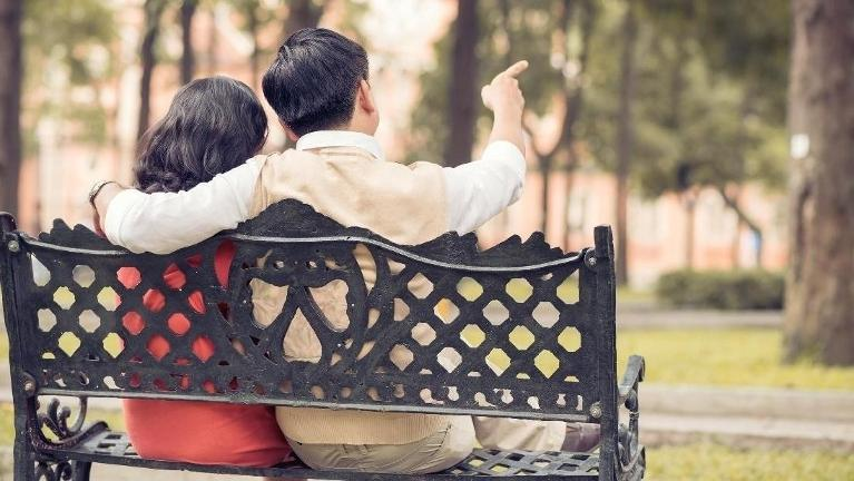 woman and man cuddling on outdoor bench